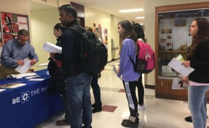 A line of students collect the paperwork to register for the Be The Match registry. (Peggy Hogan-Rao, Staff Photographer)